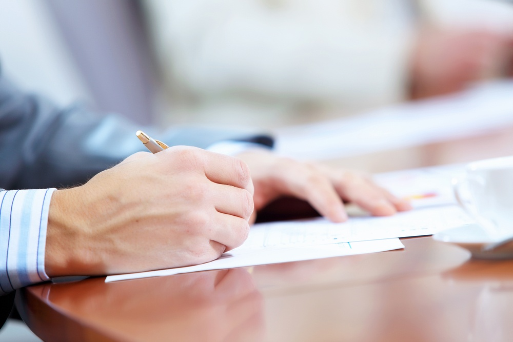 Image of businessman's hands signing documents at meeting.jpeg